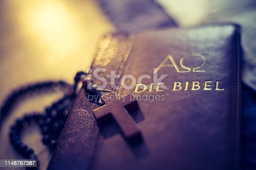istock Holy bible and rosary: Christian bible and rosary on a wooden desk 1148767387