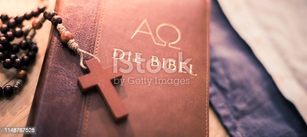 istock Holy bible and rosary: Christian bible and rosary on a wooden desk 1148767528