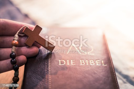 istock Holy bible and rosary: Christian bible and rosary on a wooden desk 1148767539