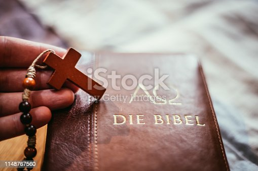 istock Holy bible and rosary: Christian bible and rosary on a wooden desk 1148767560