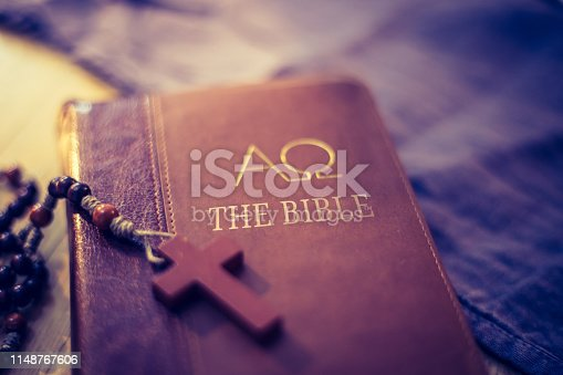 istock Holy bible and rosary: Christian bible and rosary on a wooden desk 1148767606