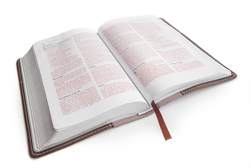 Holy Bible, isolated on white, open to Matthew chapter 5.  Words of Jesus in red.