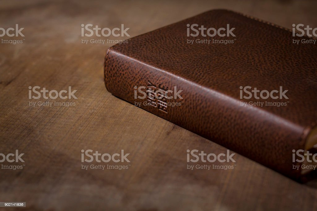 Holy Bible laying down closed on wooden table stock photo