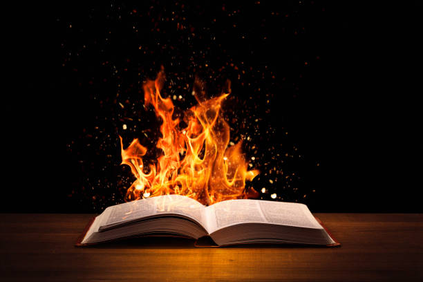 Holy Bible on fire on a wooded desk stock photo