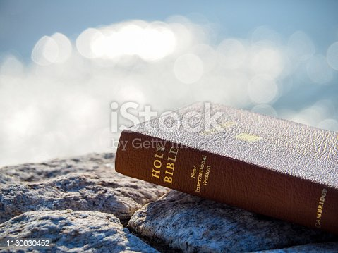 istock Holy bible on rock with  reflection  bokeh of blue sea as background 1130030452