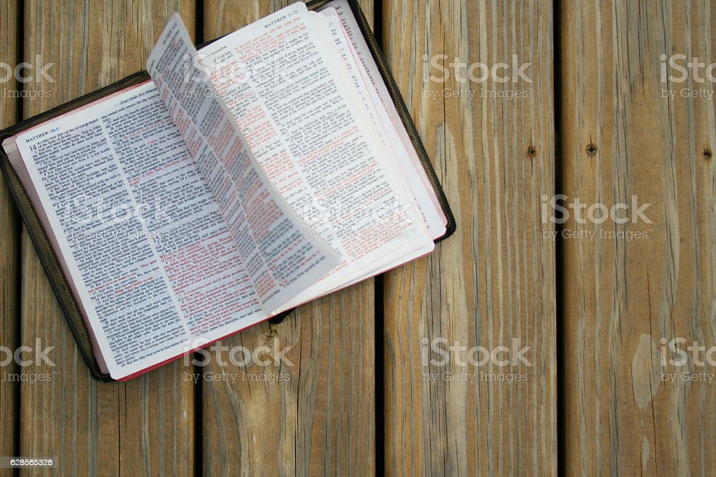 Holy Bible Turning Pages on Wooden Background stock photo