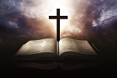 Holy Bible with a cross and a dramatic sky