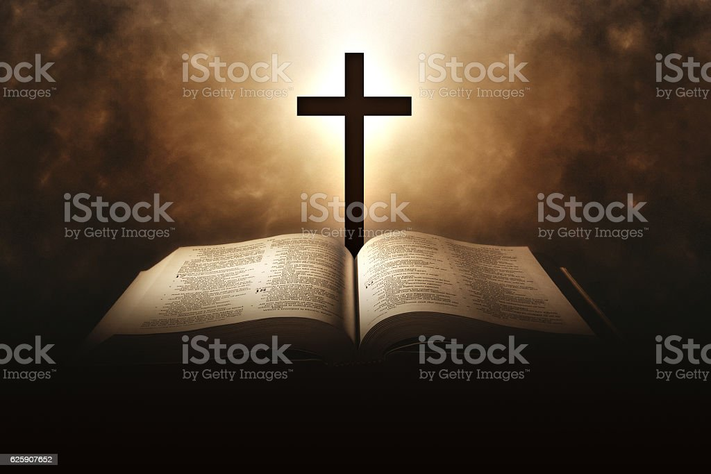 Holy Bible with a cross and a light coming from above stock photo
