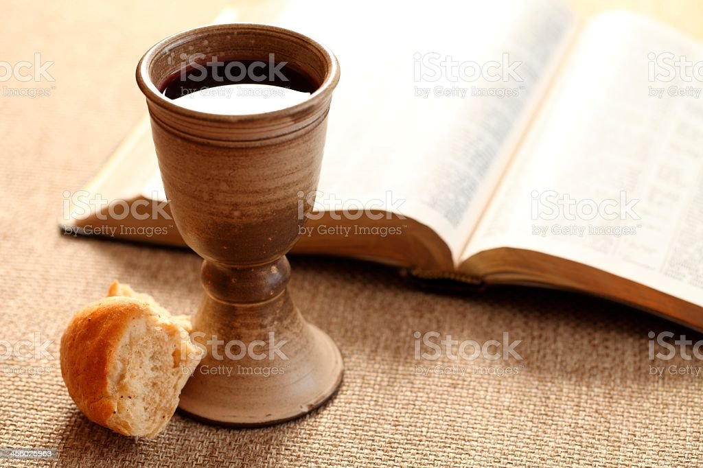 Holy communion wine and bread by open bible stock photo