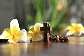 Holy Cross of rosary closeup in low angle view. Wooden rosary with Jesus Christ crucifix  and Bali frangipani flowers. Copy space on the background  for your text design. Catholic spiritual symbol.
