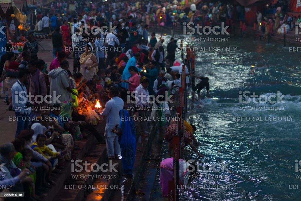 Holy ghats at Haridwar, India, sacred town for Hindu religion. Pilgrims offering floating flowers and burning candles to the Ganges River. stock photo