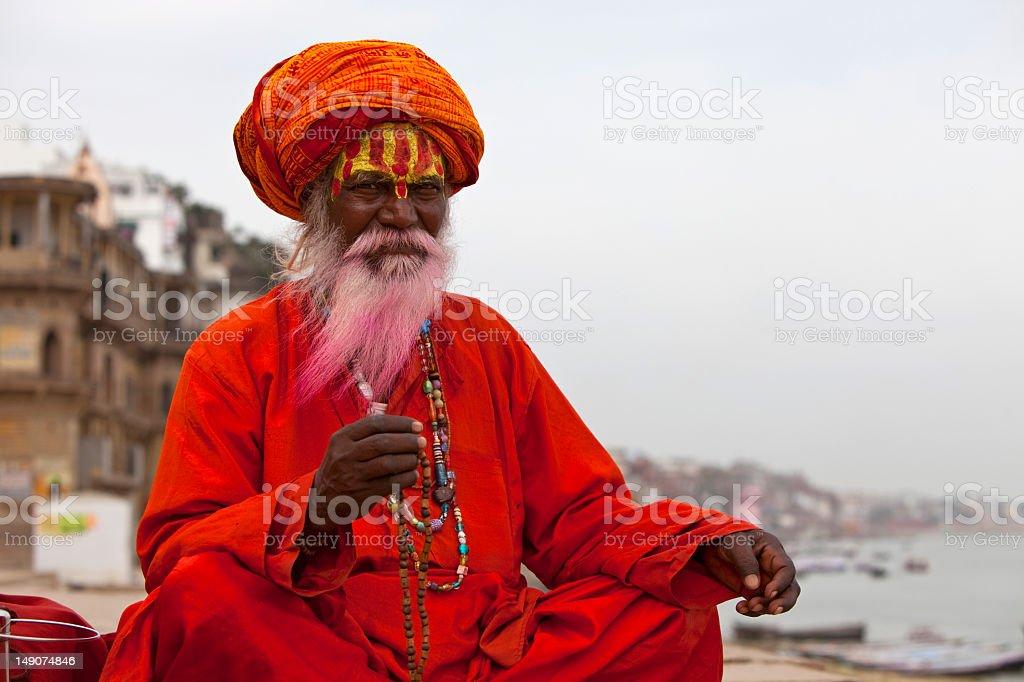 Holy Indian Sadhu wearing an orange turban with a red robe stock photo
