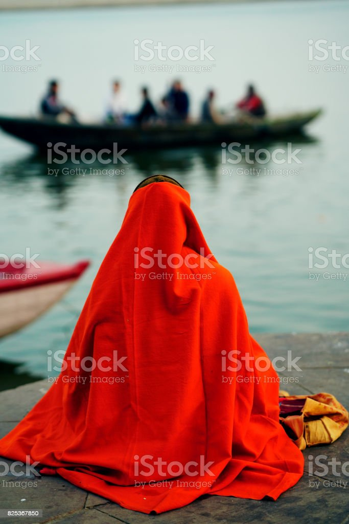 Holy Indian Sadhu wearing an orange turban with a red robe stock photo