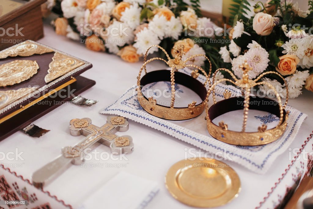 Holy matrimony in church. Golden crowns,cross,bible and candles on altar in church, religious items stock photo