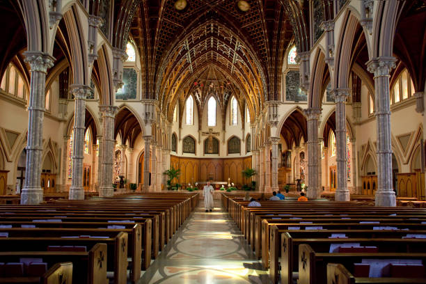 Holy Name Cathedral in Chicago Chicago, Illinois: Horizontal view of the catholic Holy Name Cathedral interior with the priest walking along the central aisle clergy stock pictures, royalty-free photos & images