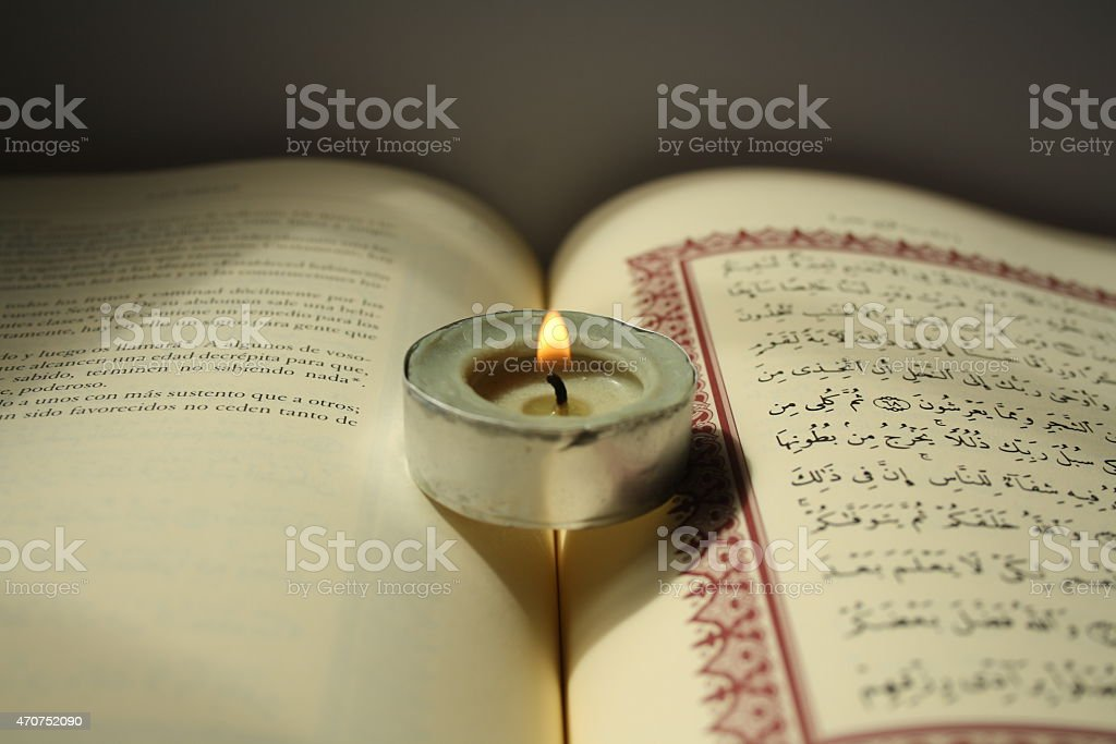 Holy Quran with a candle in the middle. stock photo