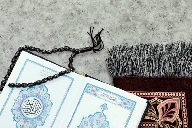 Heiliger Koran mit arabischer Kalligraphie Bedeutung von Al Quran und schwarzem Rosenkranz und Gebetsmatte – Foto