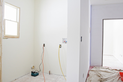 Interior wall priming and painting is in process during construction of a home addition in-law apartment.