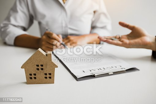 481337750istockphoto Home agents are sending pens to customers signing a contract to buy a new home. 1177832043