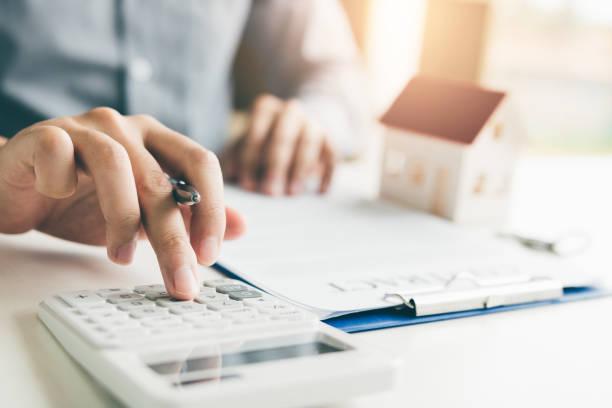 home-agents sind einen taschenrechner verwenden, um die leihfrist pro monat für den kunden zu berechnen. - eigenheim stock-fotos und bilder