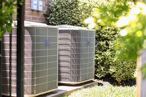 Air conditioner unit outdoors in side yard of a brick home in hot summer season.   No people.