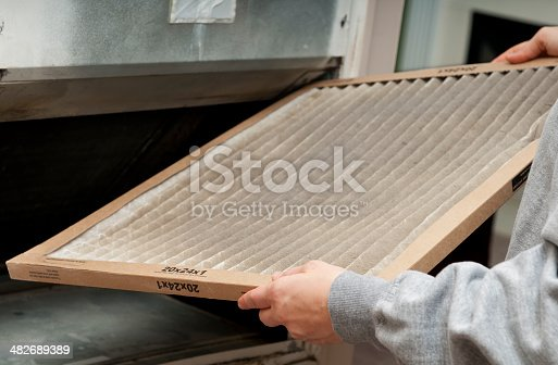 Home owner changing their dirty air filter.