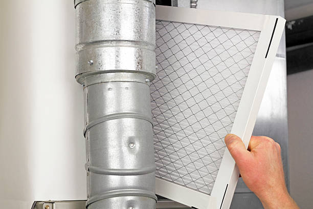 Home Air Filter Replacement Male arm and hand replacing disposable air filter in residential air furnace.. air filter stock pictures, royalty-free photos & images