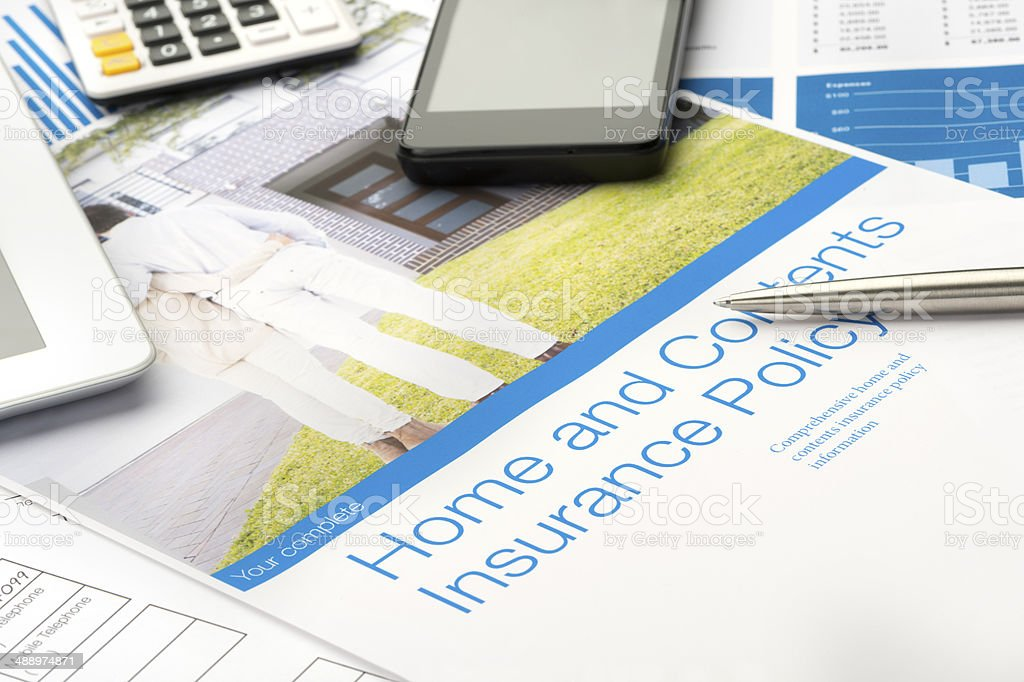 Home and contents insurance document with paperwork and technology....