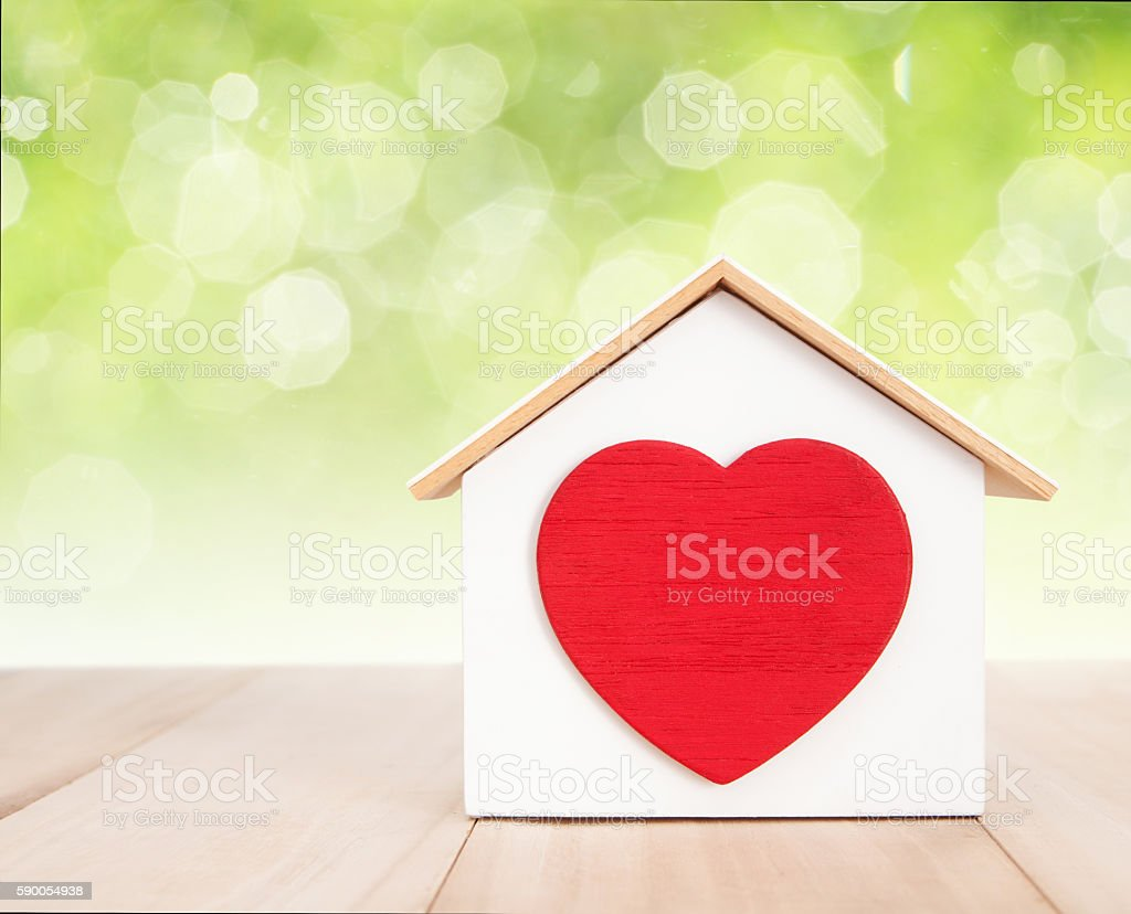 Home and red heart on wood with bokeh background - Photo