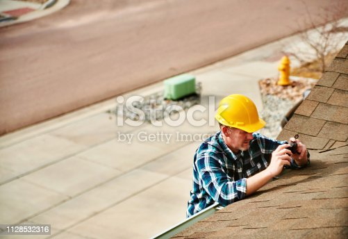 534196421istockphoto Home Appraiser or Home Inspector surveying roof of property 1128532316