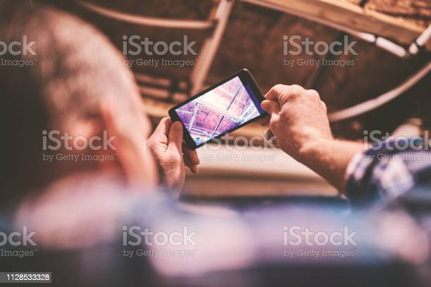 Home Appraiser Or Home Inspector Using Smartphone To Photograph Insulation And Plumbing Stock Photo - Download Image Now