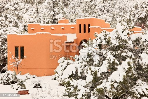 Southwest styled home during blizzard with snow flurries and accumulated snow on surrounding bushes and trees.  Sedona, Arizona, 2012.
