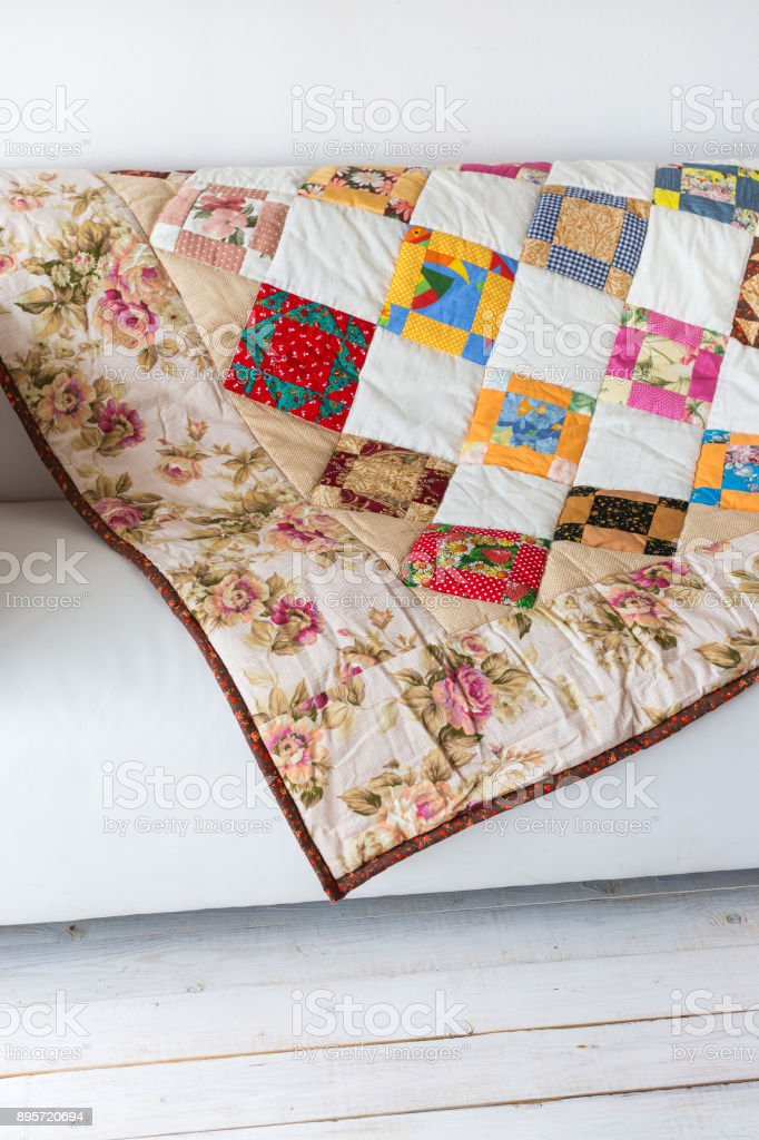 home, art, craft concept. blanket gently crafted by hands have symmetrical ornament of rhombuses and fringed by beige satine material with roses pictutes on it stock photo
