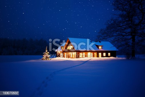 Illuminated house with christmas tree beside it in wintery scene with footpath to it.