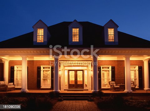 Cape Cod House with all it's light on with a beautiful blue skyline in the background.