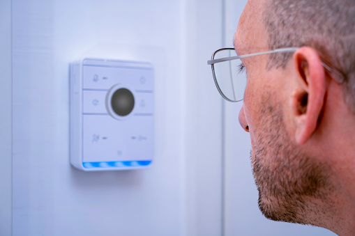 Caucasian man authenticating himself by scanning his face at the home automation hub using artificial intelligence and a web cam face scanner.