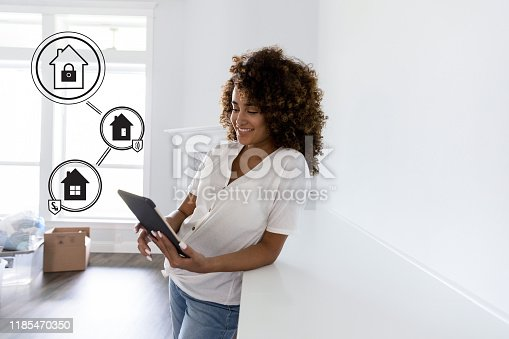 Confident young woman programs automated home security with a digital tablet.