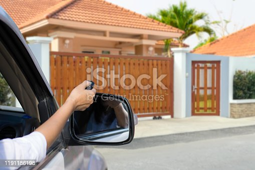 Woman in car,hand holding and using remote control to open the automatic door with modern home blurred background. Auto gate or garage, electric door concept.