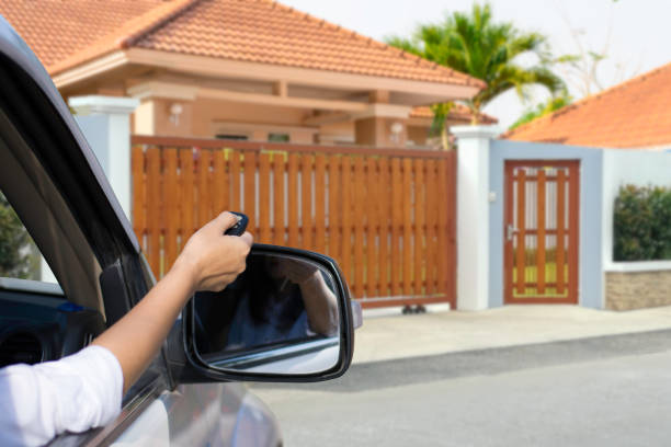 home automation Woman in car,hand holding and using remote control to open the automatic door with modern home blurred background. Auto gate or garage, electric door concept. automatic stock pictures, royalty-free photos & images