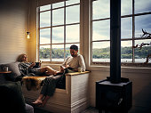 Shot of a young couple reading books while relaxing together in their holiday home