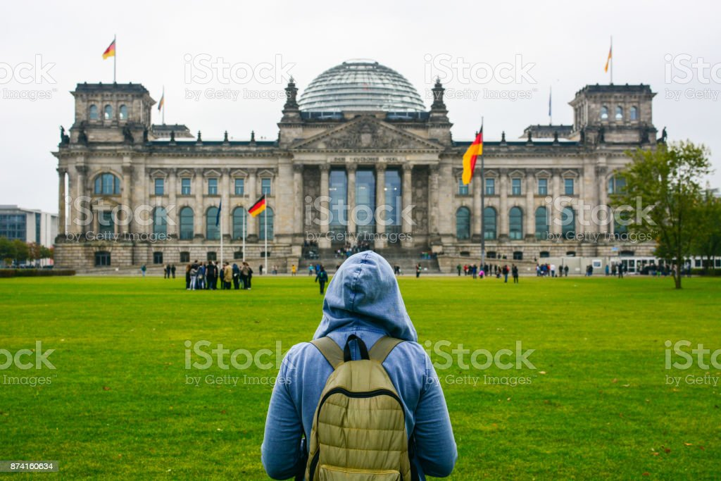 Home away from Home: Young woman with backpack looking at Bundestag building stock photo