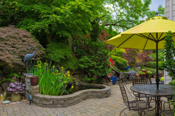 strona główna podwórku hardscape i bujne rośliny krajobrazu z meblami ogrodowymi na brukarz ceglane patio - staw woda stojąca zdjęcia i obrazy z banku zdjęć