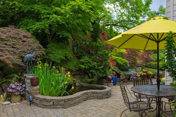 home backyard hardscape and lush plants landscaping with garden furniture on paver brick patio - staw woda stojąca zdjęcia i obrazy z banku zdjęć