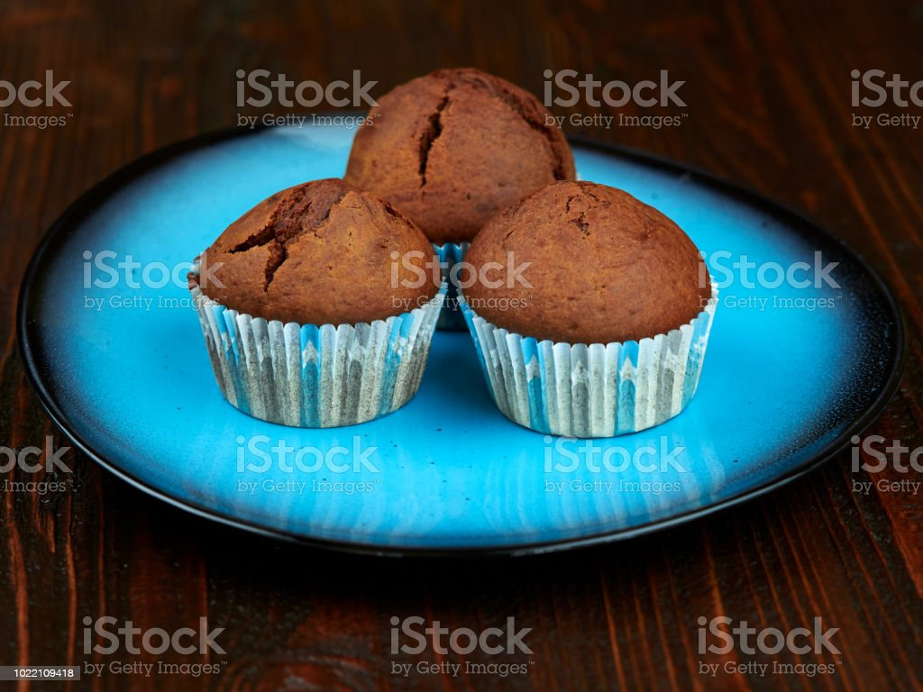 Home baked cocoa muffins set on a blue plate stock photo