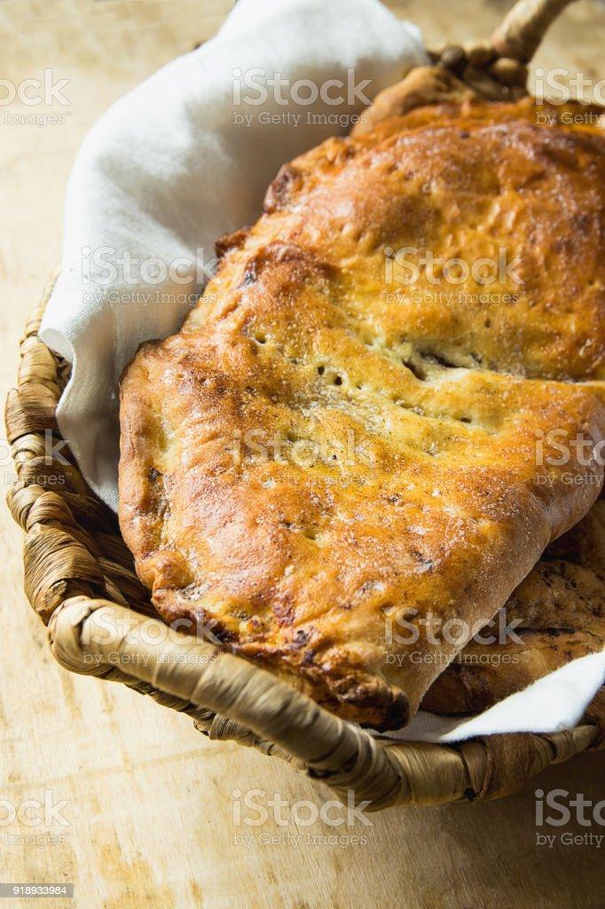 Casa assado italiano pastelaria Calzone com torta de maçã doce passas canela preenchendo a cesta de vime no guardanapo de linho branco. Tabela de madeira envelhecida. Interior da cozinha rústica. - foto de acervo