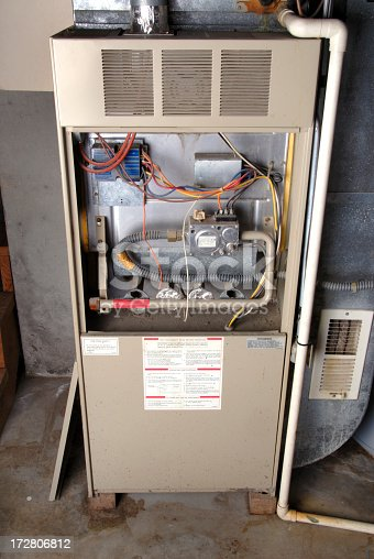 Old-technology, natural-gas furnace in a typical basement installation of a home.