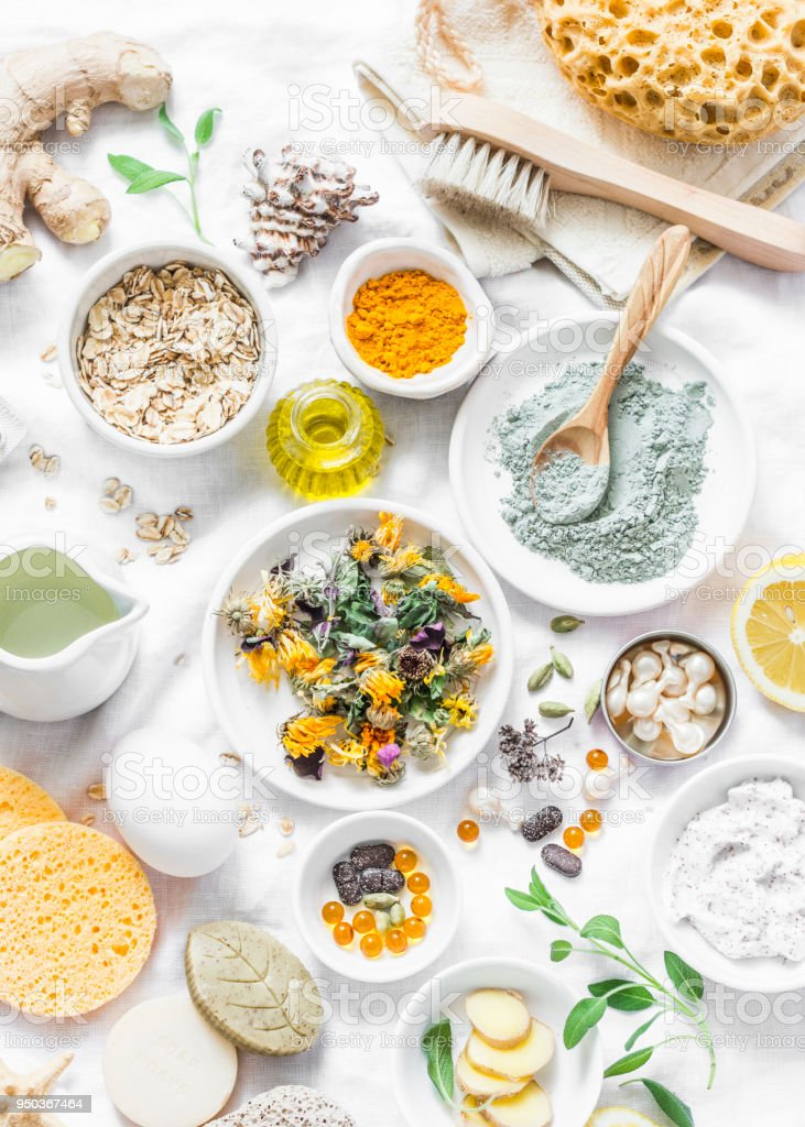 Home beauty products - clay, oatmeal, coconut oil, turmeric, lemon, scrub, dry flowers and herbs, sponges, soap, facial brush on light background, top view. Skin youthfulness, beauty concept. Flat lay stock photo