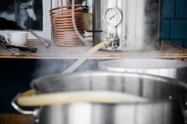 Home Brewing Kit and Pouring Craft Beer Wort into the Boil Kettle. stock photo