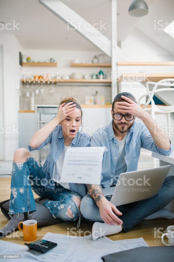 Portrait of a young couple calculating their bills at home