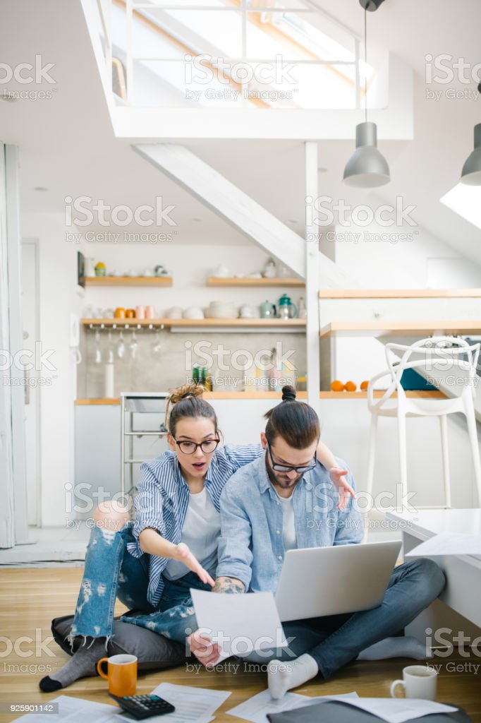 Young couple calculating their bills at home